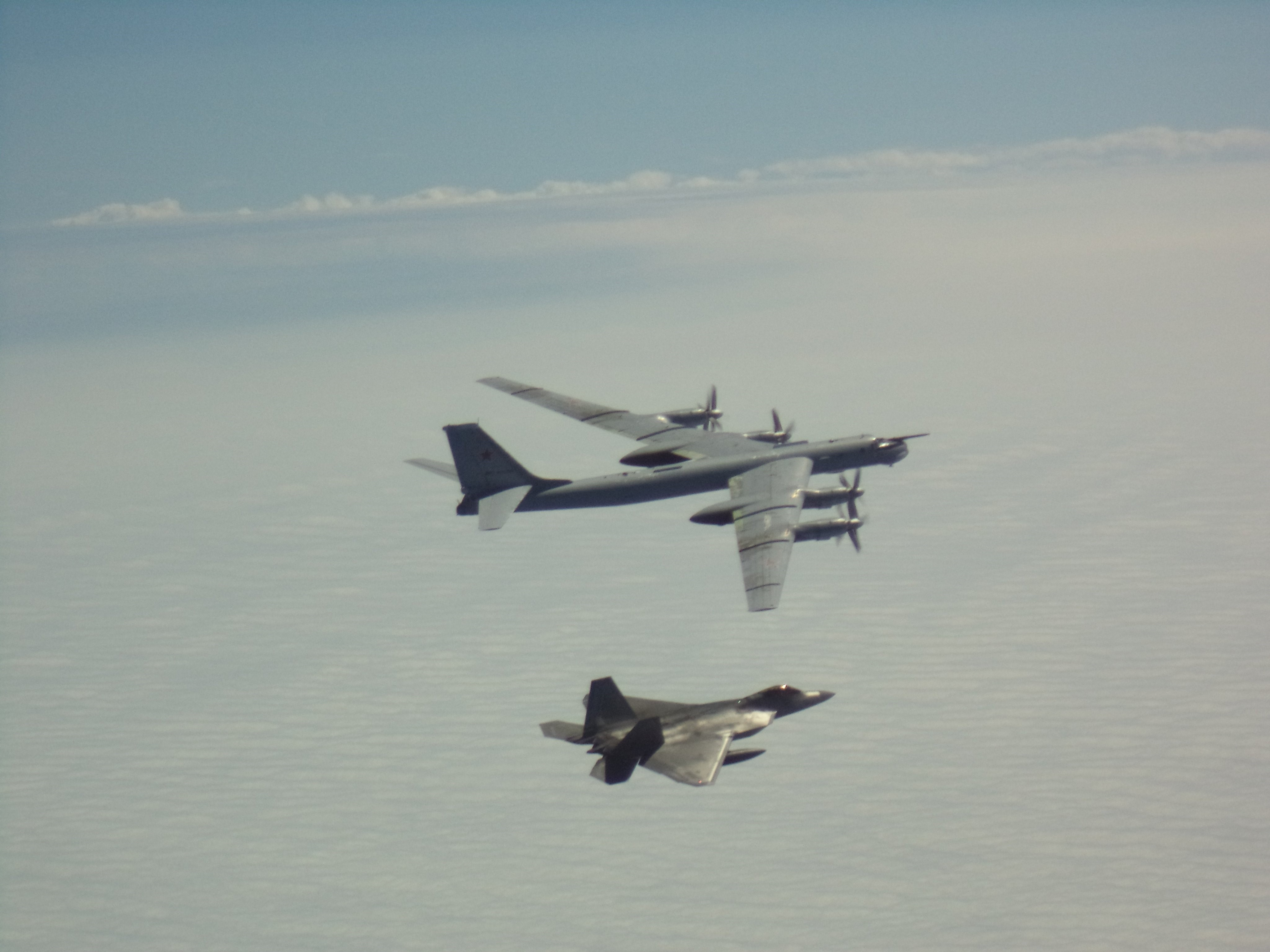 Photo of an F-22 flying below a Russian bomber.