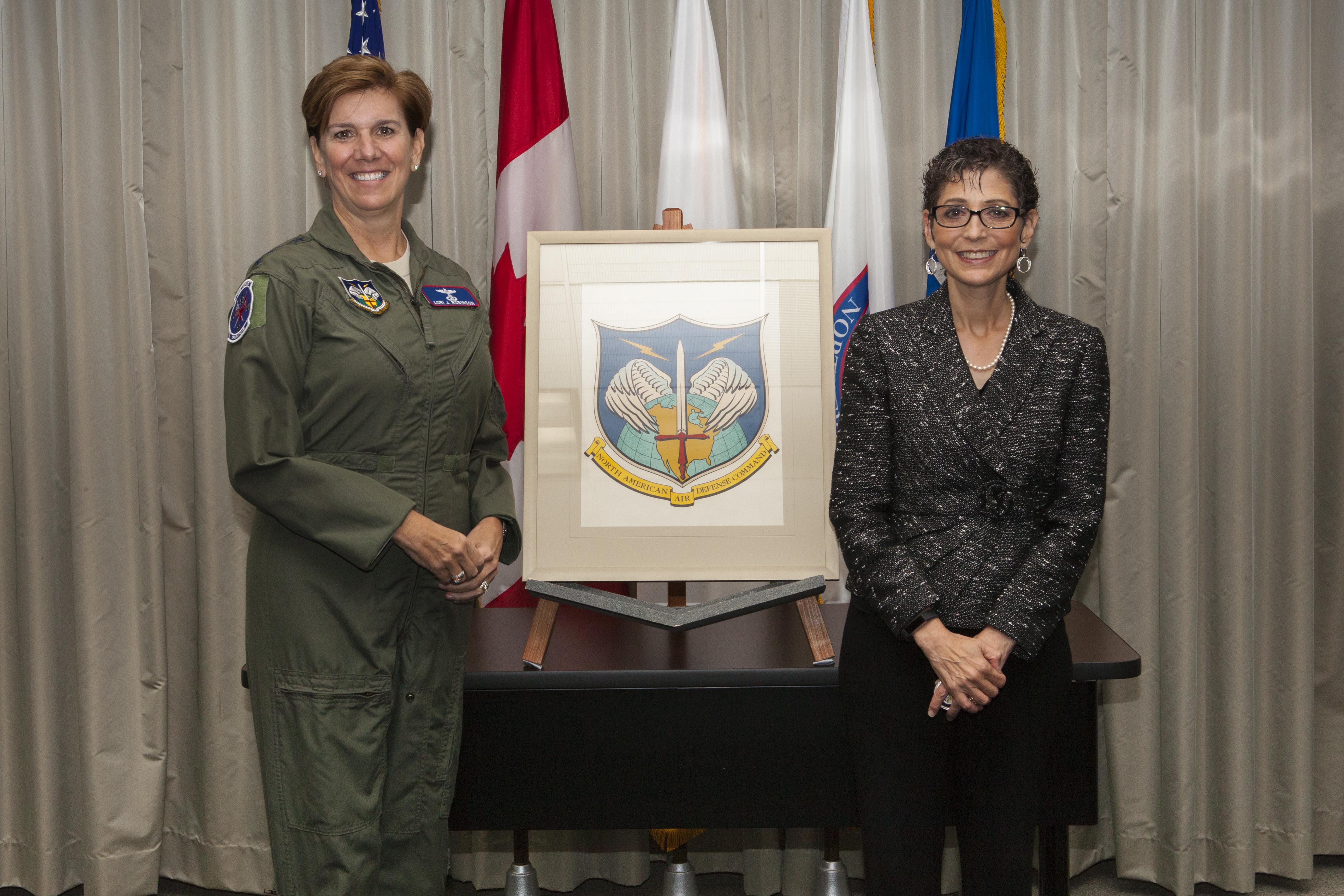 Gen. Robinson and Ms. Mona Rowe pose with original NORAD emblem art